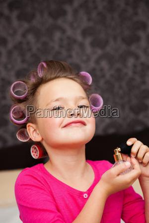 girl with hair curler spraying perfume