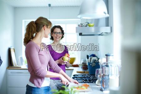 two women preparing vegetables in kitchen