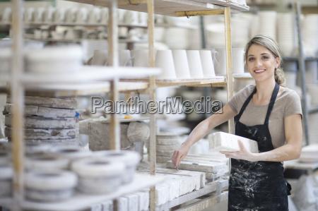 potter arranging clay blocks onto shelf