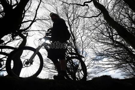 silhouette man mountain biking