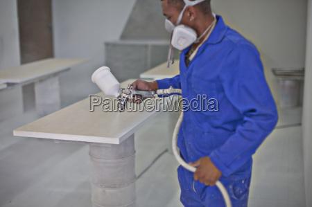 man spraying wooden plank in carpenters