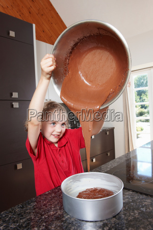 girl pouring cake mix into cake