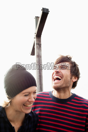 couple laughing under mountain cross
