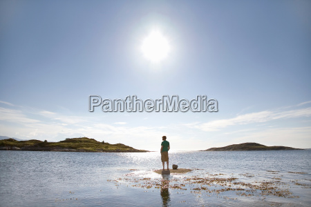 man standing on rock in sea