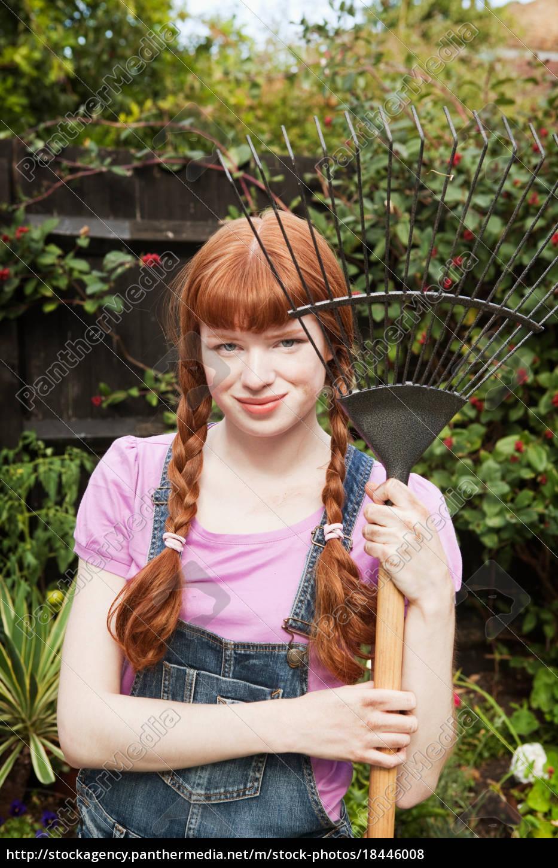 woman, holding, grass, rake, in, garden - 18446008