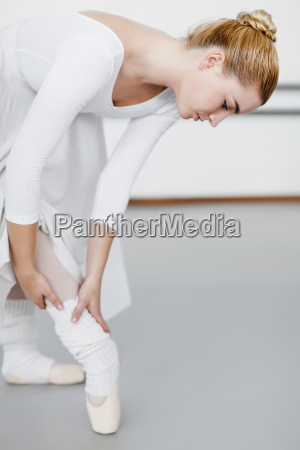 ballet dancer examining hurt ankle