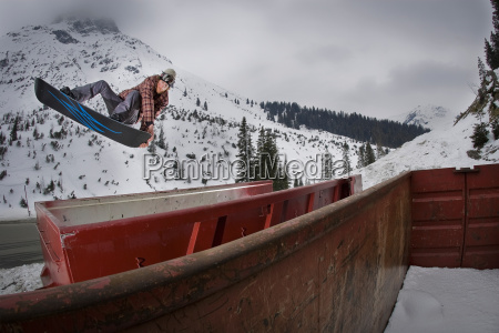 snowboarder jumping over train cars