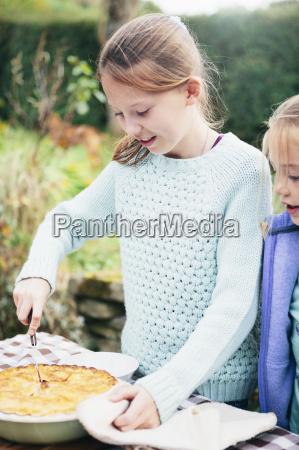 girl cutting homemade pie