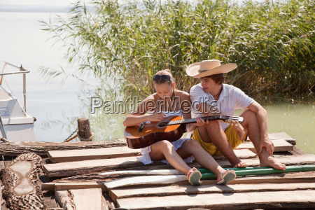 young couple sitting together on jetty