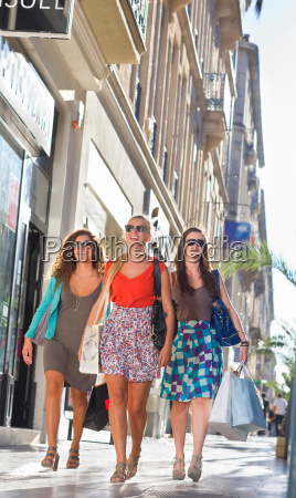 young women walk in street with