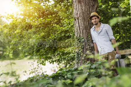 young man leaning against tree with