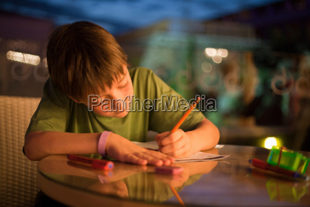 boy concentrating on writing homework