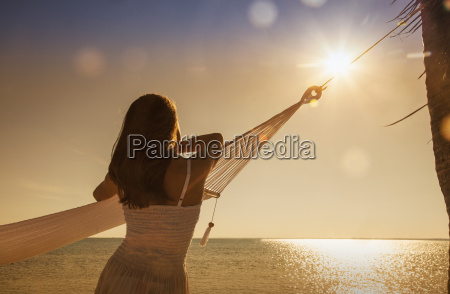 young woman leaning on hammock looking
