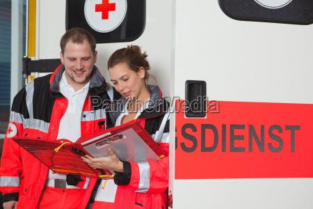 ambulance team examining file at coach