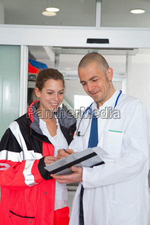 paramedic and doctor examining file