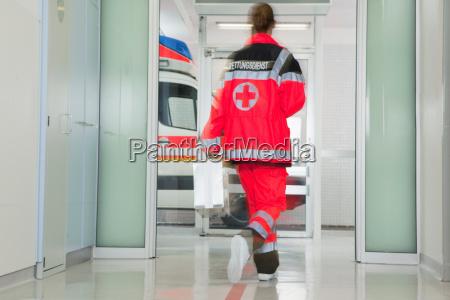 back of paramedic rushing at hall
