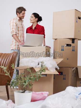 young couple with boxes and laptop