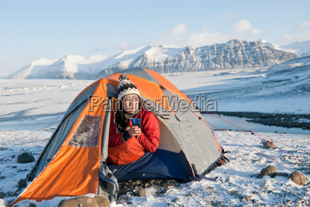 hiker drinking in camping tent in
