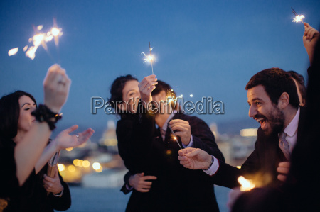 friends hugging and holding sparklers at