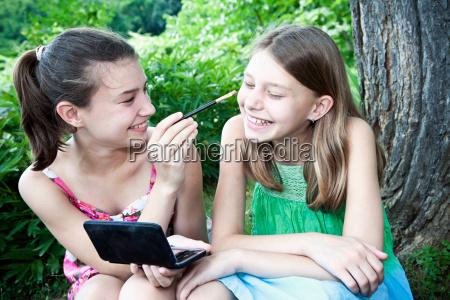 girl putting make up on sister