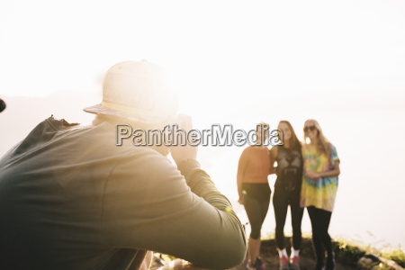 young man photographing female friends at