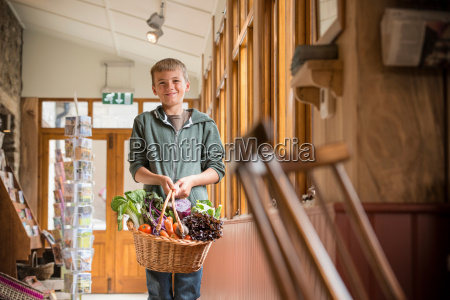 portrait of boy holding basket of