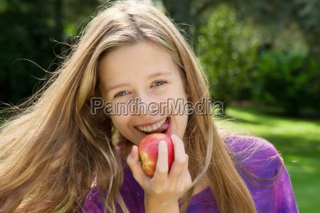 smiling girl eating apple in park