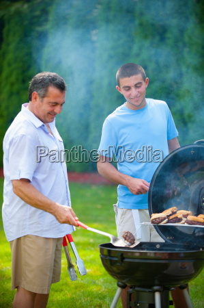 father and son grilling outdoors