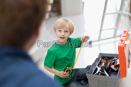 boy with measuring tape and toolbox