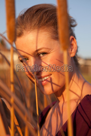 smiling woman standing in wheat field
