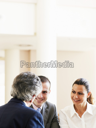 two businessmen and woman in meeting