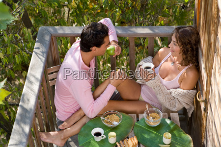 romantic couple eating in tree house