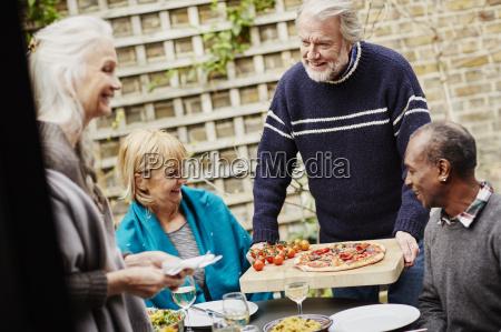 senior man serving friends pizza in