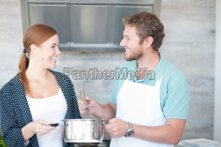 young man and woman cooking in