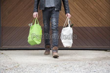 teenage boy carrying reusable shopping bags