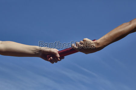 hands of female relay runners passing