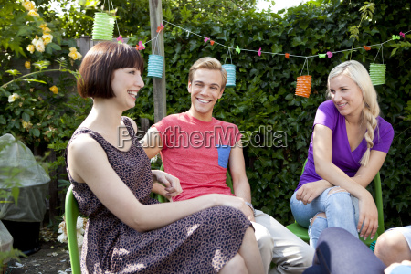 young adult friends in garden chatting