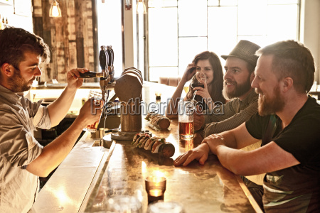 friends drinking beer at hipster bar