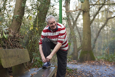 mature male runner tying trainer laces