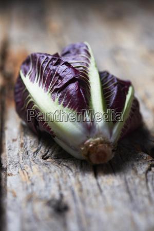 whole purple lettuce on rough wood