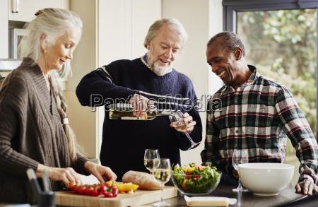 senior man pouring wine in kitchen