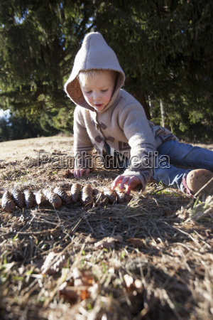 female toddler playing with pine cones