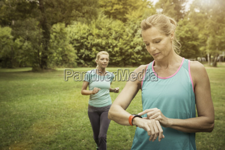 mature women jogging in park checking