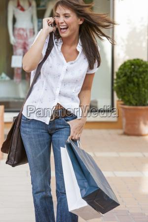 young female shopping carrying shopping bags