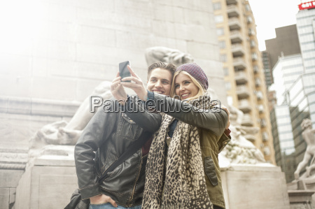 young couple taking smartphone selfie on
