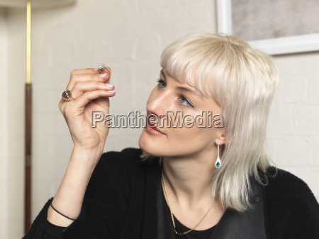 female jeweler examining ring in jewellery