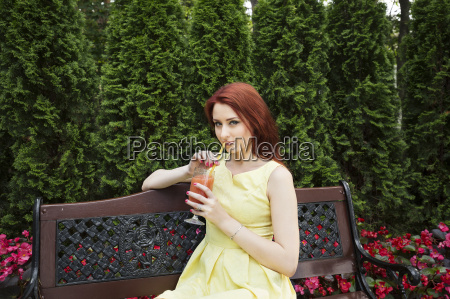 young woman drinking juice on park