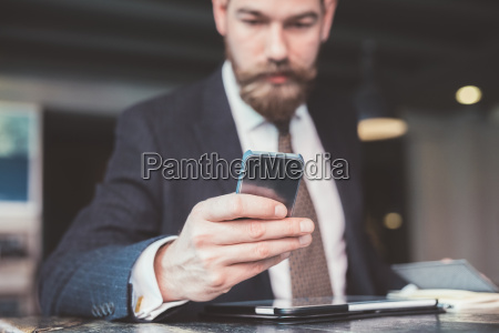 businessman reading smartphone update at cafe