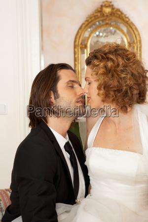 young bridal couple kissing