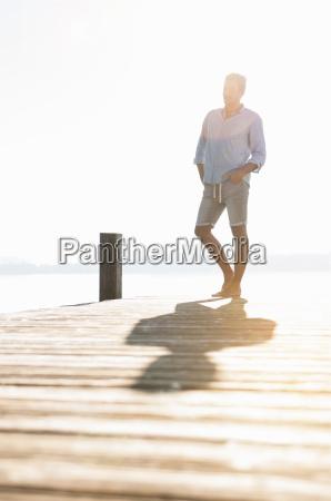 young man on sunlit lake pier